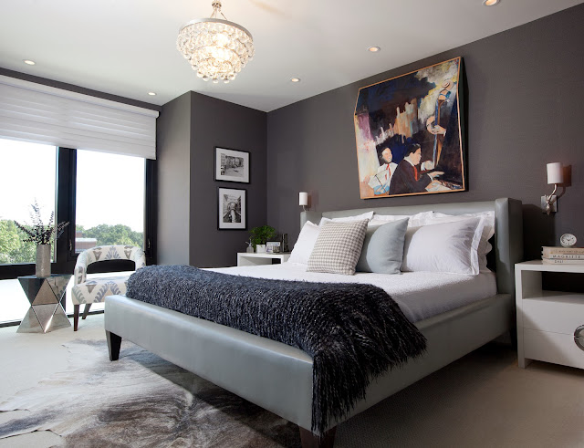 Sleek and modern grey master bedroom with a leather platform bed, crystal chandelier and floor to ceiling windows