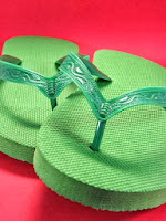 A pair of lime green plastic flip flops with a red backdrop.