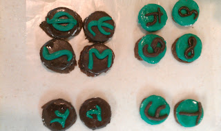 Cookies decorated with mathematical and greek symbols, including phi, psi, sigma, pi, tau, h-bar, delta, zeta, an integral sign and an infinity sign.
