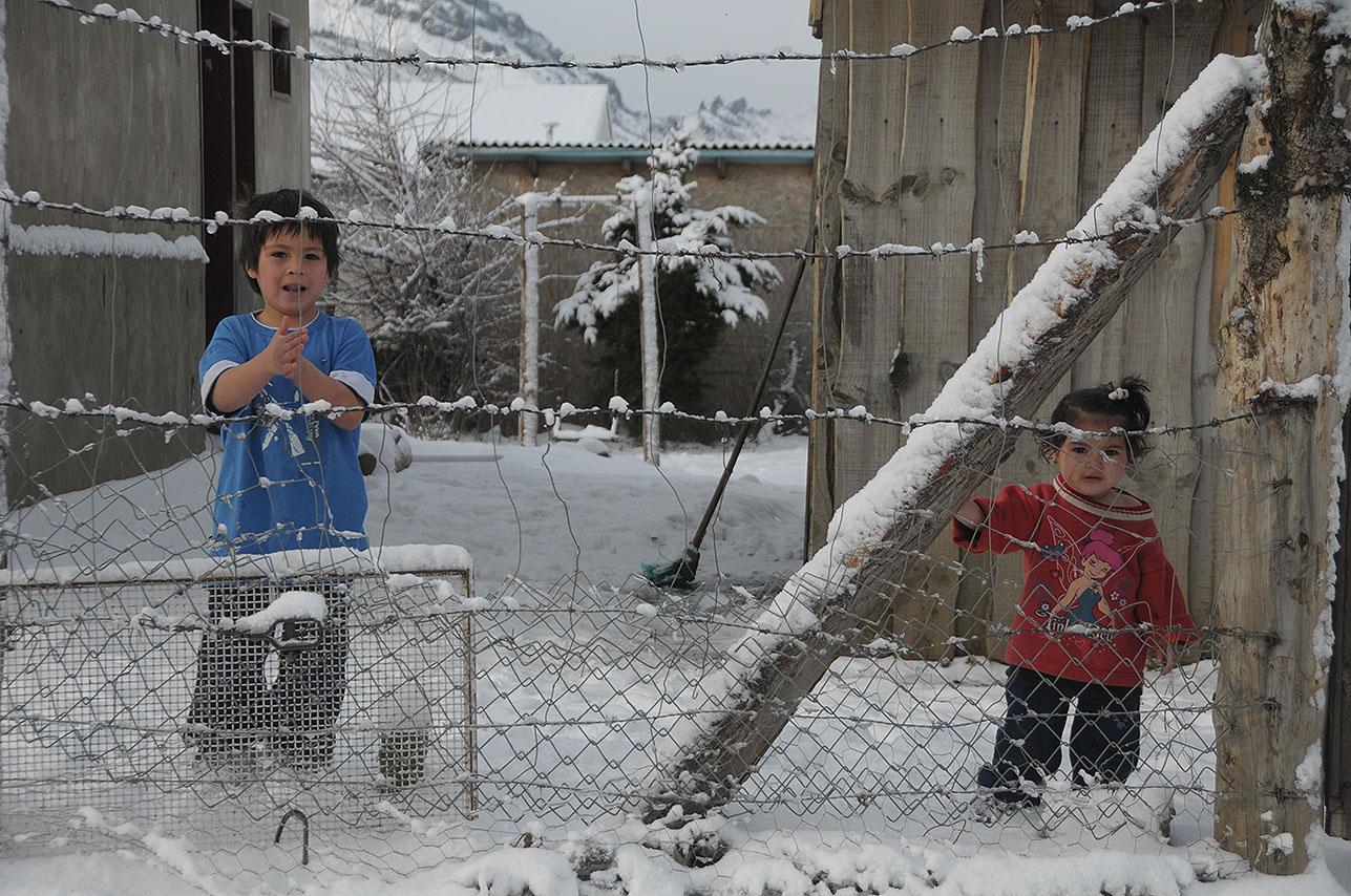 Dos niños desabrigados en la nieve en una vivienda precaria