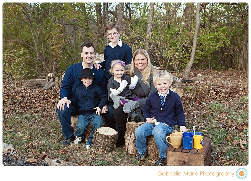 Family of six enjoys sits on tree trunk seats around a fire drinking hot chocolate