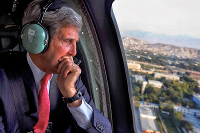 US Secretary of State, John Kerry looks out of the window of a Black Hawk helicopter at the city en route to ISAF Headquarters after an unannounced visit to meet with Afghan President Hamid Karzai, in Kabul on October 11, 2013.  US Secretary of State John Kerry arrived on an unannounced visit to Kabul to try to advance troubled negotiations with Afghanistan on some US troops staying in the country after 2014