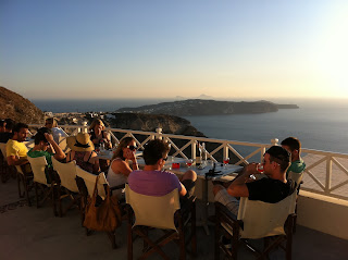 Our group drinking wine at sunset with the southern arm of Santorini in the distance.