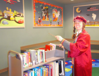 Cynthia M. Parkhill, dressed in red bell-sleeved 'wizarding robes' over gray cardigan and slacks, waves a 'wand' over library shelving cart with books on it. Colorful Halloween-themed poster-boards are shown in background; one says 'Happy Halloween.'