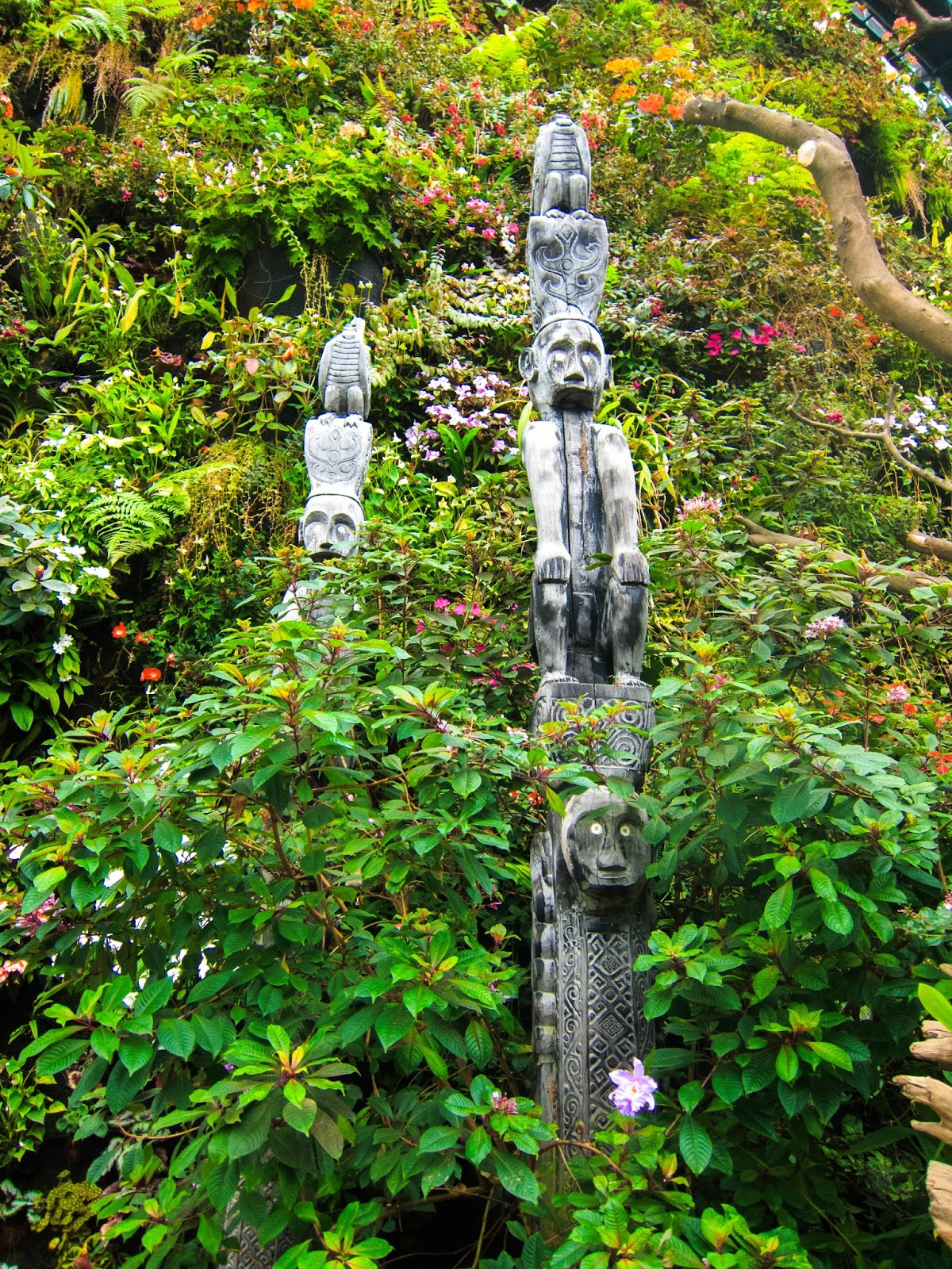Monkey statues surrounded by colourful flowers on mountain wall in Cloud Forest, Gardens by the Bay in Singapore | Svelte Salivations - Travel