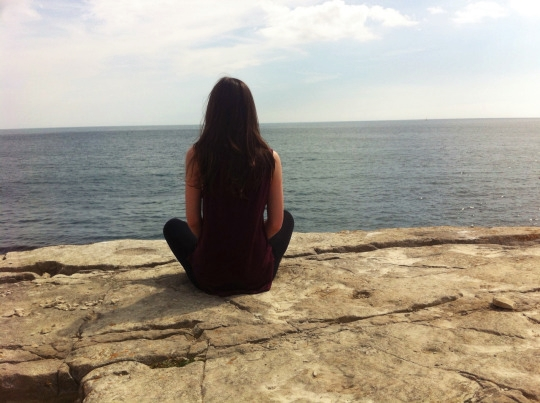 meditating on rock by sea