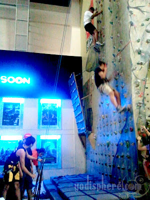 People handling the belays while two people are climbing walls