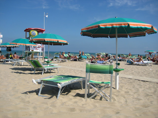 A photo of umbrellas and deck chairs on the beach in Rimini, Italy.