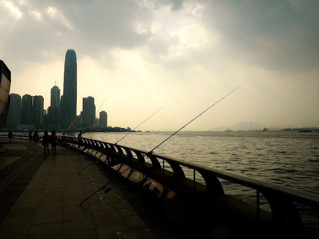 Fishing poles at sunset / dusk beside Victoria Harbour, taken from Wan Chai / Exhibition Centre Pier, and overlooking Central skyscrapers of Hong Kong