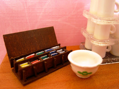 Modern dolls' house miniature tea bag box, bowl and stack of mugs on a tabletop.
