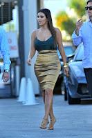 Kim Kardashian famous curves in a gold dress