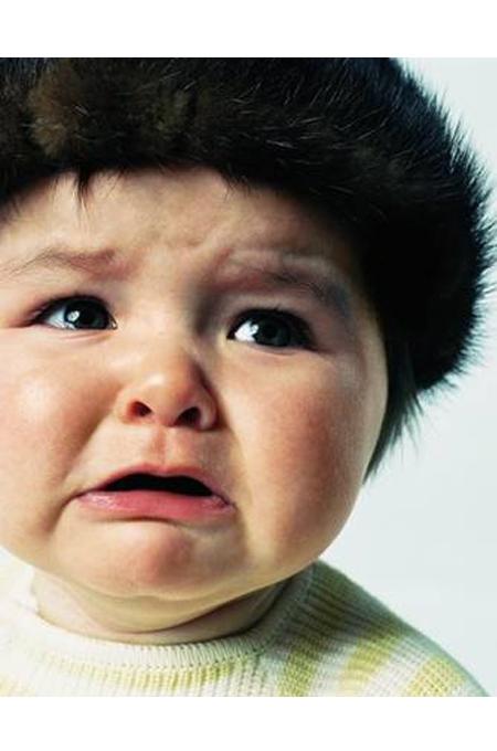صورة طفل يرتدي قبعة من الفرو يبكي وتملأ عيونه الدموع