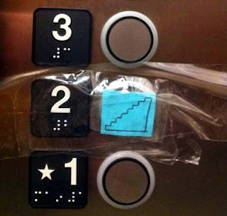 Elevator button panel with the second floor button covered with a drawing of stairs taped over the button, the raised number 2, and the Braille number)