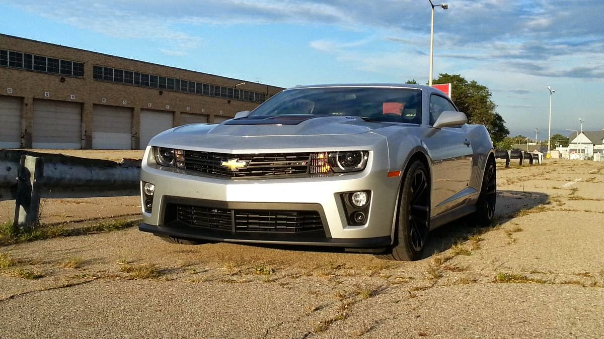 "THE ZL1 IS THE ULTIMATE CHEVY CAMARO FOR THE STREETS  ASSOCIATE EDITOR GRAHAM KOZAK: I'm not sure what else to say about this 2015 Chevrolet Camaro ZL1 coupe -- it's an OK display pedestal for a tremendous engine. It's interesting to drive the ZL1 after some time in the Challenger SRT Hellcat. The eight-speed Dodge I drove had more power, of course, but there's a certain point after which you just can't put it down to pavement on stock tires.  The manual transmission definitely improved driver engagement here; there's something about building up revs and dropping into second gear that's just addictive. You'll want to give your best Picard ""Engage!"" just before you launch forward.  On the other hand, more energy spent shifting means less focus to devote to making sure the wheels are pointed straight. The blown 6.2-liter V8 has a well of grunt to draw from that it's both wide and deep. The specter of fourth-gear wheelspin at speed is haunting, but also exciting.  The downsides are the car's weight, interior appointments and price. Here, you get a cabin that features all of the tech you could want, but not much of the refinement. There's suede here and there, but also a lot of hard plastic. I doubt we'll get a major refresh before we get a new Camaro, but who knows?  You could get a Chevy Corvette for this price. Or a Hellcat, almost. But people who want a Corvette will get a Corvette, and Mopar fans will get a Hellcat. Don't expect a BMW M4 with a bowtie on it (although, how cool would an M4 with this motor and transmission be?!) and you won't be disappointed by the ZL1.     2015 Chevrolet Camaro ZL1 Coupe right side  Tooling around town in the 2015 Chevrolet Camaro ZL1 Coupe is actually quite nice, refined and almost tame. 2015 Dodge Challenger SRT Hellcat review notesCAR REVIEWS 2015 Dodge Challenger SRT Hellcat review notes EDITOR WES RAYNAL: This blown V8 so thoroughly dominates the driving experience, it's hard to write about anything else -- from the addictive, wonderful sounds to the near-unfathomable oomph, it's about as dominant as I can imagine. As we've written before, driving this car makes you feel like you're getting away with something.  I gotta admit this car intimidates me some. Tooling around town, it's actually quit nice, refined and almost tame. The ride is fine, the steering direct, the clutch take-up and weight just fine for around town, though there's so much torque here almost any gear works…  There is a bit of steering correction needed on sloppier roads but good Lord, look at the tires. Of course there's gonna be a little. It's really not bad at all.   Then I leg it, and I always had in the back of my mind the notion this thing is gonna pitch up on to the sidewalk any second. Not to say it doesn't handle well -- for its size and weight, it does. The stability control system allows for some fun, in other words it's not overly sensitive/restrictive. Turn off the traction control and slide it around some. Good times…  The car looks good, and I like the ZL1 body mods -- bigger air openings, bulging hood, front spoiler. Cool. The interior looks nice, as well.  2015 Chevrolet Camaro ZL1 Coupe left side  The supercharged V8 in the 2015 Chevrolet Camaro ZL1 Coupe thoroughly dominates the driving experience. ROAD TEST EDITOR JONATHAN WONG: With the Dodge Challenger SRT Hellcat stalking around beating its chest with 707 hp, the 580 hp that this 2015 Chevrolet Camaro ZL1 packs doesn't seem like much does it? Except that 580 hp is a whole lot of power. It's crazy to sit back and think about how many cars are available today that have engines producing north of 500 hp. Sure, you have all those pricey performance models from the luxury German automakers that will put at least a $100,000-sized dent into your bank account. But for $60K, anyone can walk into a Chevy dealership and then drive away with a Camaro with close to 600 hp. That's kind of nutty.  But then you get behind wheel of the Camaro ZL1 and idle around town with the magnetic suspension softened and just roll gingerly onto the throttle, and it's a relatively relaxed experience. The underlying Camaro chassis still feels substantial and steering is weighty, but not overly so. The ZL1's ability to behave like a normal car is something I've always respected about it in comparison to the outgoing Ford Mustang Shelby GT500, which seemed like it was ready club you over the head with a lead pipe the moment you let your guard down.  When it comes time to wheel the ZL1, it again doesn't feel like this overpowered monster. Most people with a ZL1 are probably just going to mash the throttle in a straight line to impress their friends and do a smoky burnout or two, but I doubt they'll be looking for a bunch of twisty roads to blaze. It is a heavy boy, tipping the scales at 4,120 pounds. However, you can have some fun throwing it around turns where there is descent grip, considering its weight that you do feel in the corners. The good news is that there isn't a bunch of roll, thanks to the magnetic suspension keeping things fairly tidy. Push a little too hard and the front end washes out with a little chatter felt through the steering wheel.  2014 Chevrolet Camaro ZL1 Convertible review notesCAR REVIEWS 2014 Chevrolet Camaro ZL1 Convertible review notes Graham is correct in saying that the car is all about the supercharged LSA V8 engine. It makes all the right rumbly V8 noises, but most important of all is that power. I'm personally a road-course person who likes to round corners, but even I can't deny that it's a thrill to have a ton of horsepower propel you forward in a straight line at an alarming rate. The six-speed manual features fluid shifts, and the clutch pedal isn't super heavy and difficult to modulate.  Besides the car's weight, the cabin is still a disappointment. The microfiber inserts on the dash and wrapping the steering wheel and shift knob help break up the hard plastic cave, but the large areas of exposed hard plastics look and feel cheap. Being a Camaro, it's still difficult to see out of the darn thing with blind spots big enough to fit semi-trucks in. The optional Recaro seats are great, though.  For the street, the ZL1 is the ultimate Camaro that can be handled by a competent driver. Personally, I would have myself a Z/28 with the optional air conditioning (hey, it gets hot here in Michigan in the summer!) if I was shopping for a Camaro. I do look forward to seeing what Ford will do with the future Mustang GT500 and its independent rear suspension, which I'm guessing won't behave like it wants to murder you, and seeing how that stacks up to the ZL1. And of course, there's the Challenger SRT Hellcat which has the horsepower bragging rights and a much improved interior. It handles like a battleship, but the novelty of having 707 hp is neat, and would make you king of the streets. Given the choice between a ZL1 and Hellcat, I think I would go with the Mopar as a street car."