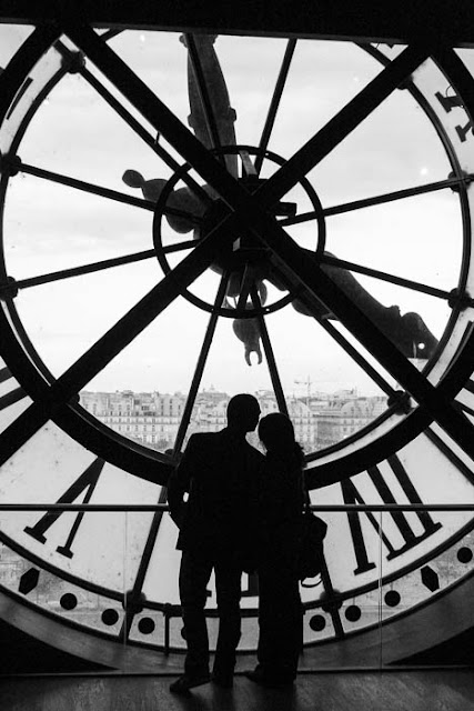 couple kissing in front of the window clock at Musee d'Orsay