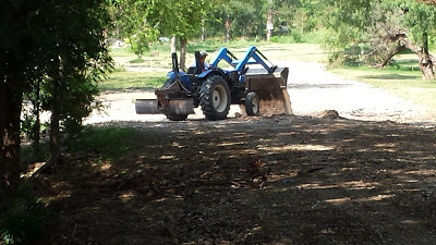 Tractor filling the holes and leveling the roads