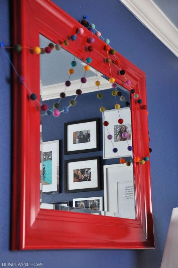 Spray painted mirror with colorful felt ball garland is fun in a kid's room