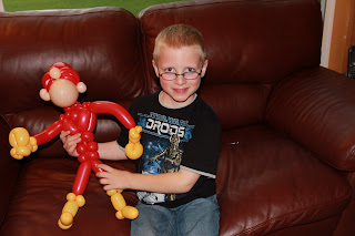boy sitting on the couch with a balloon animal that looks like a super hero
