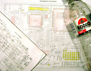 [Image: Papers titled BLOCK DIAGRAM and SCHEMATIC DIAGRAM lying on the table or floor. The schematic diagram is colored in. A bottle of energy drink to the right.]