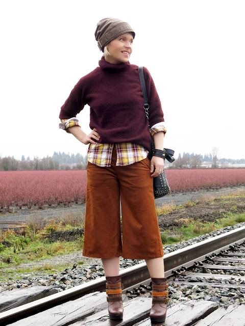 styling a maroon wool turtleneck with a plaid shirt, faux-suede culottes, and platform booties