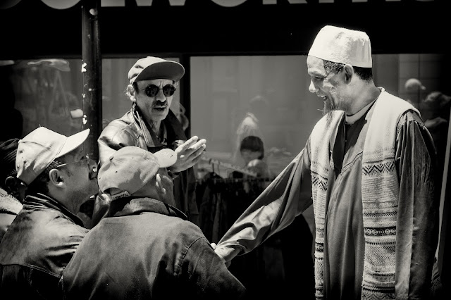 Street photograph depicting a muslim cleric being introduced to a group of men in Cape Town South Africa.