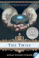 cover of The Thief by Megan Turner is book one in the Queen's Thief series shows two hands holding a stone pendant with a blue crystal in the middle