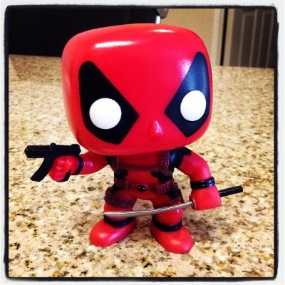 A picture of Tiny Deadpool, a small bobblehead dressed in a red and black outfit that covers every inch of his body. His overlarge head features round, solid white eyes set within elongated black triangles. He brandishes a small black gun and a small silver katana with more weapons strapped onto his costume.