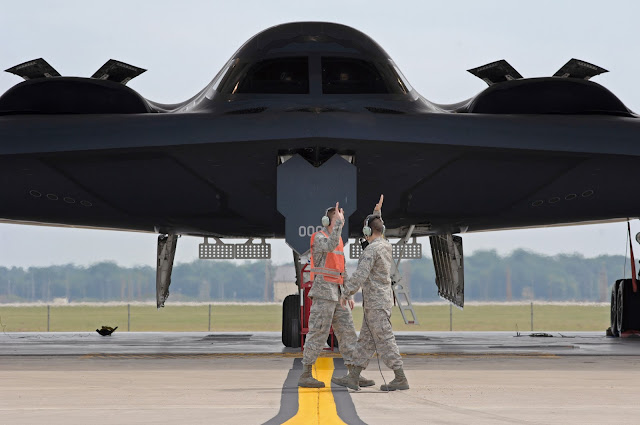 Two airmen  start the high-five salute as they prepare to launch the first B-2 Spirit