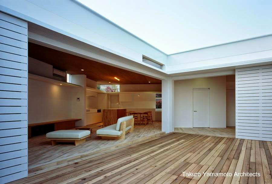 Patio con deck de madera en el centro de la casa