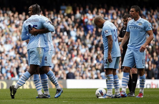 Vincent Kompany pulls away Mario Balotelli, who is arguing with Aleksandar Kolarov