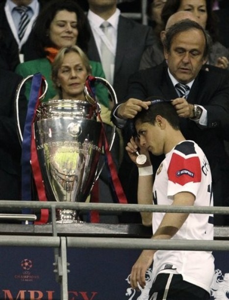 Manchester Uniteds Javier Hernandez Walks Past The Trophy As He Receives His Medal From UEFA President Michel Platini After Barcelona Won Champions