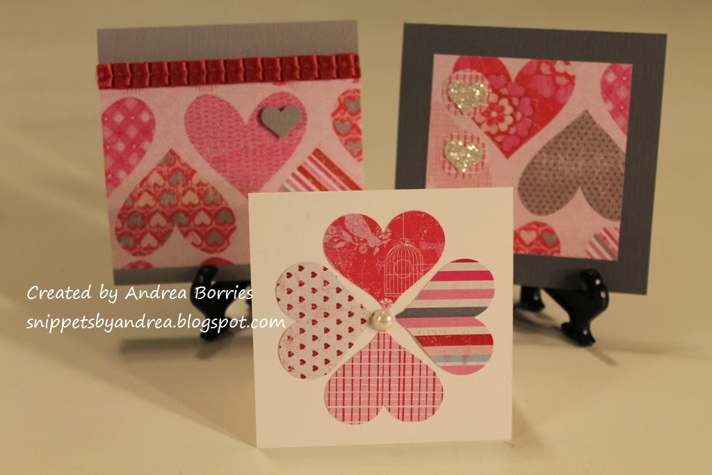 Three valentines: two with layers of heart-patterned paper and one with four hearts punched from coordinating papers and arranged in a flower shape.