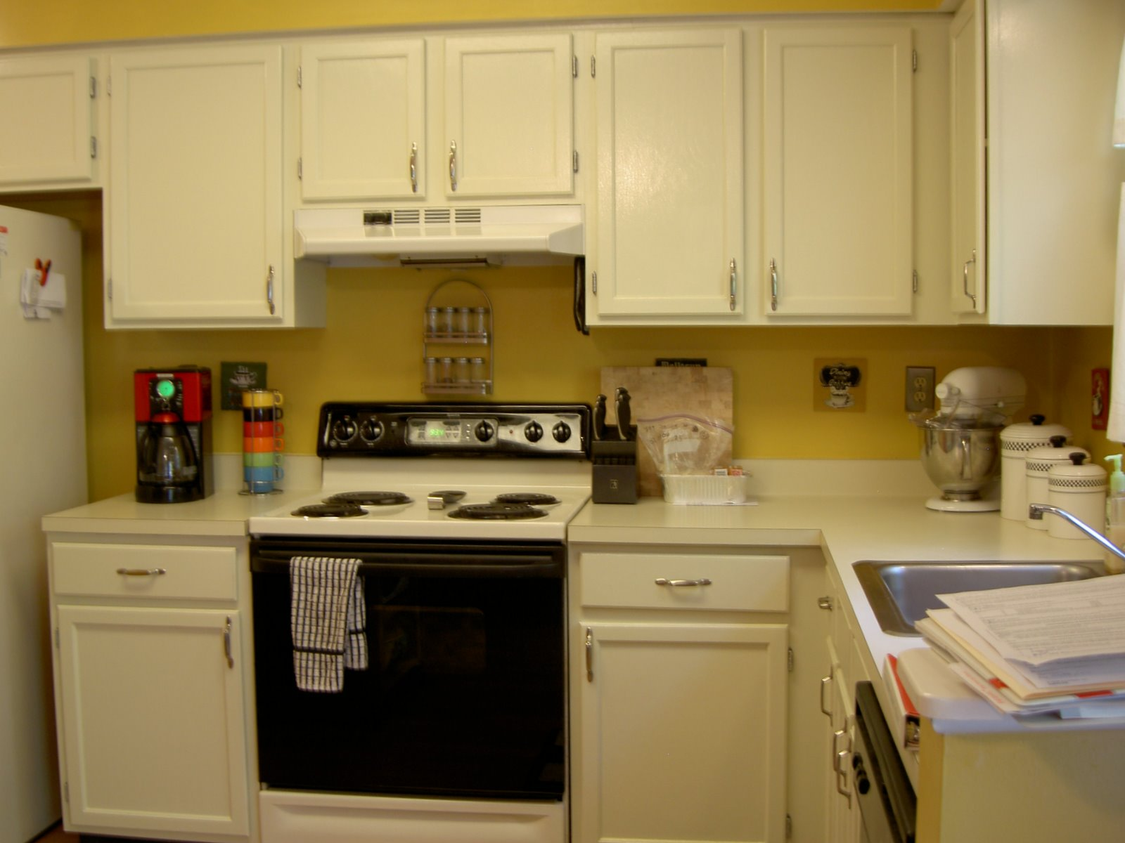 Off White Cabinets Silver Handles Visible Hinges And Black Appliances