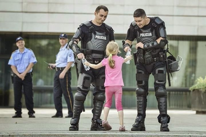 35 moments of violence that brought out incredible human compassion - girl hands water to two officers
