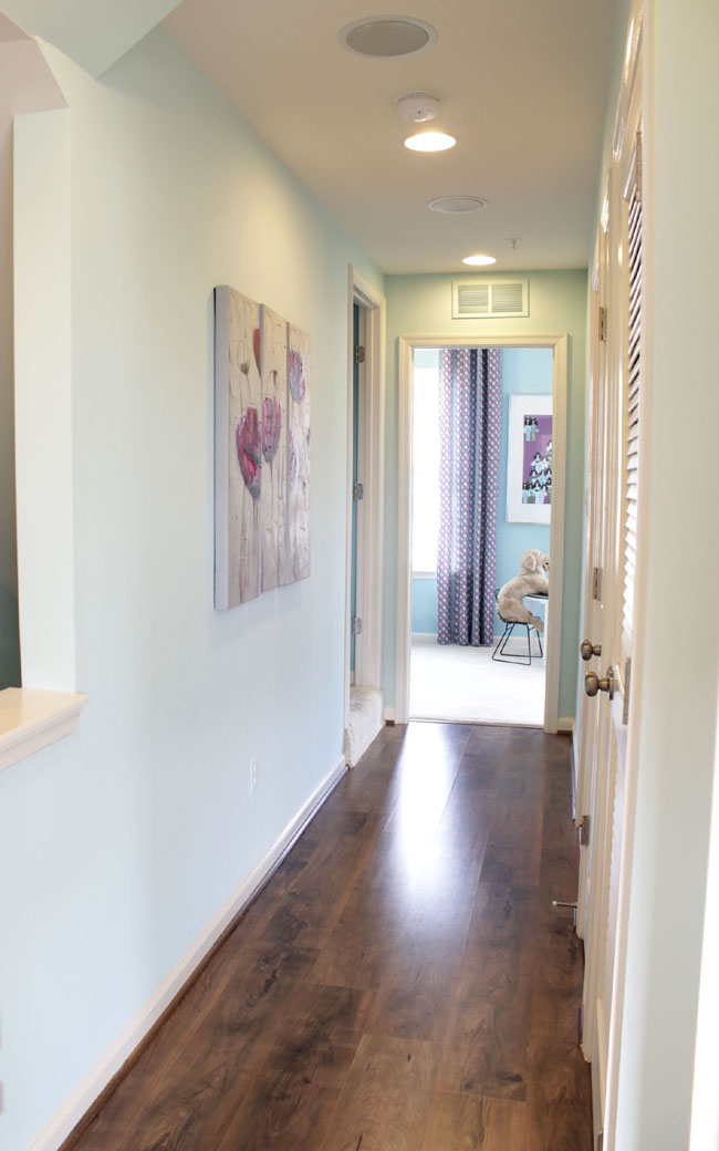 a simple hallway without clutter with hardwood floors by Miller and Smith