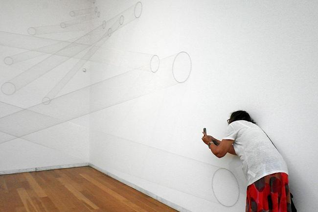 Canto de uma sala de exposição em que foram montados fios de uma parede à outra, de tal forma que, ora parecem tubos ora simples traços de um desenho. Encostada à parede direita, uma mulher tirando uma fotografia ao conjunto