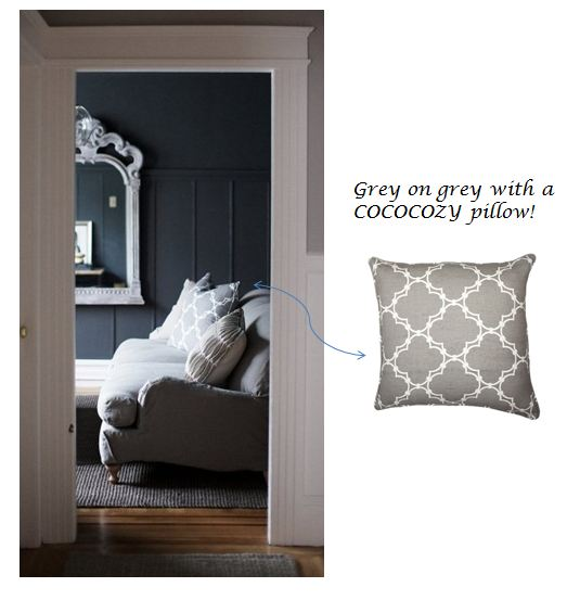 Grey Nbaynadamas pillow on a grey sofa in a living room with dark grey walls and a traditional white mirror