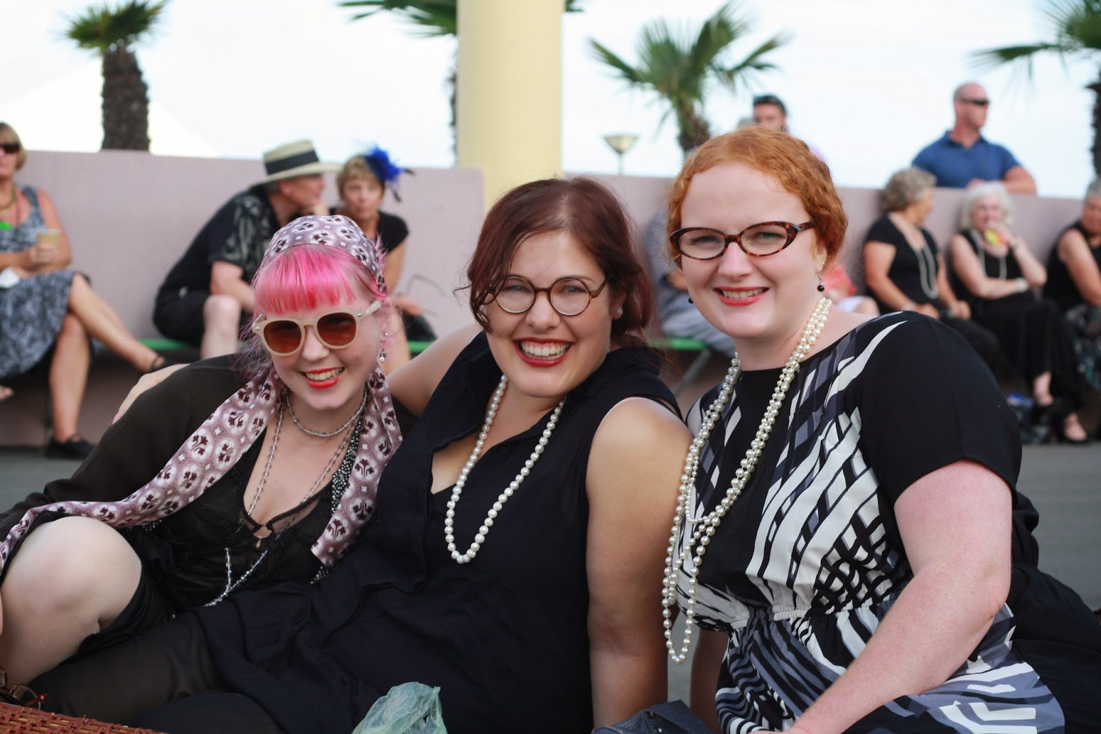 Three girls, in art deco costume and pearls, smiling.