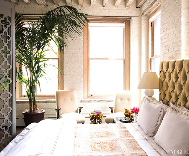Zani Gugelmann's bedroom in her NYC loft with Boomerange chairs, a fern and white bedding
