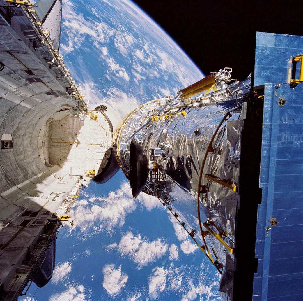 In this April 25, 1990, photograph taken by the crew of the STS-31 space shuttle mission, the Hubble Space Telescope is suspended above shuttle Discovery's cargo bay some 332 nautical miles above Earth. The Canadian-built Remote Manipulator System (RMS) arm, controlled from in-cabin by the astronaut crew members, held the huge telescope in this position during pre-deployment procedures, which included extension of solar array panels and antennae. Credit: NASA
