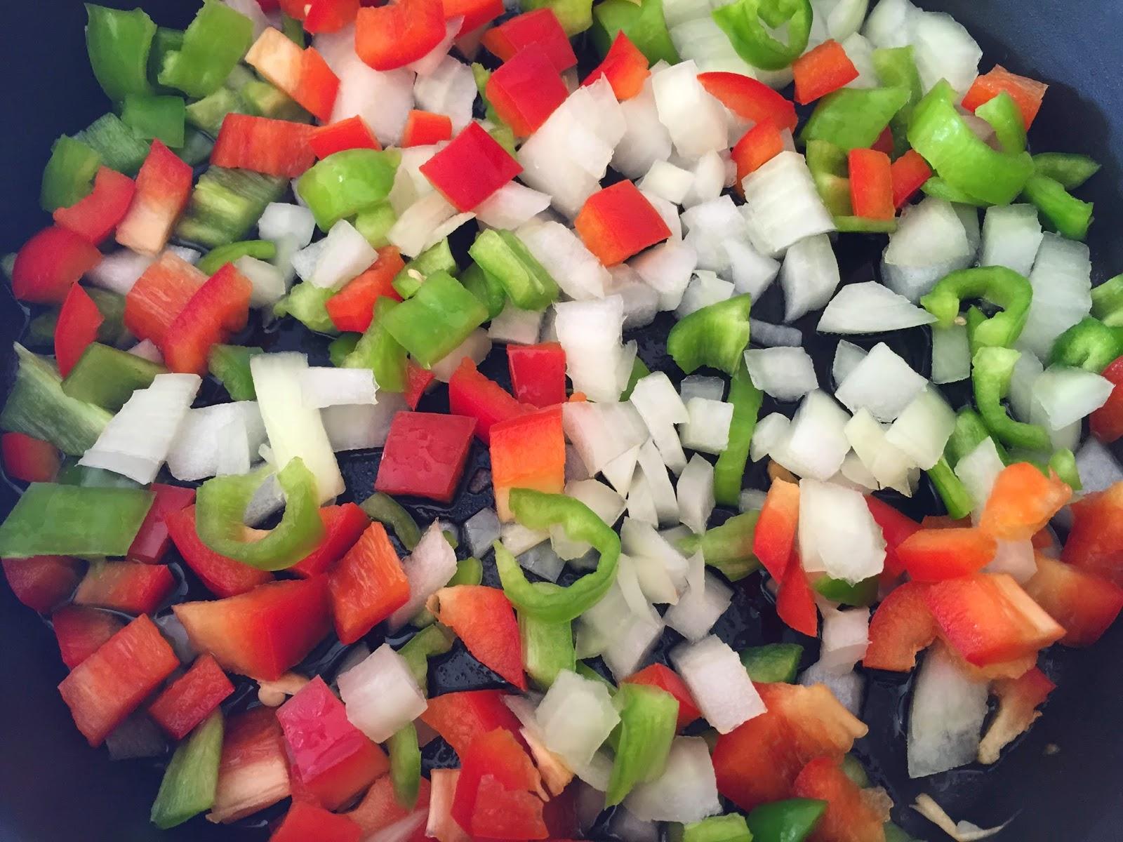 Espaguetis con verduras y salsa de soja, friendo cebolla y pimientos rojo y verde.