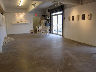 an exhibition area with gallery lighting a computer controlled studio kiln available for rent and a loading dock with garage doors artist studio lighting