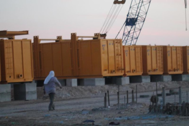Picture of worker walking by yellow construction trailers on the Kingdom Tower construction site