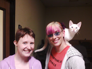 Left to right: A short very fair person with short brown hair and a big smile, a slightly taller less fair person with pink and purple hair, blue glasses, and a big smile, and a surprised looking white cat on their shoulder.