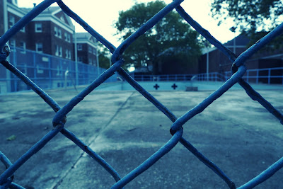 A photograph in gray tones is taken up close to a chainlink fence overlooking an empty public pool. A red brick building is to the left, in the distance.