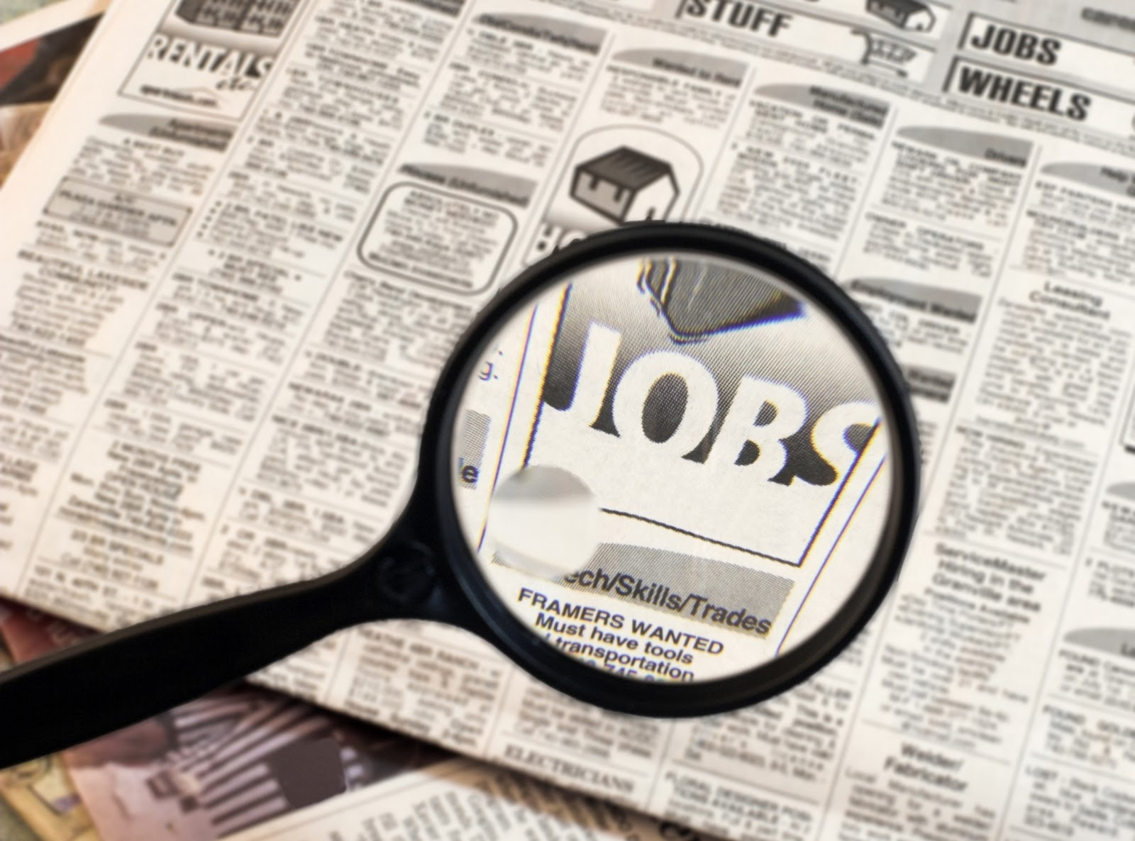 Magnifying glass over newspaper job listing