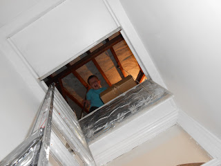 boy in attic retrieving cardboard storage boxes
