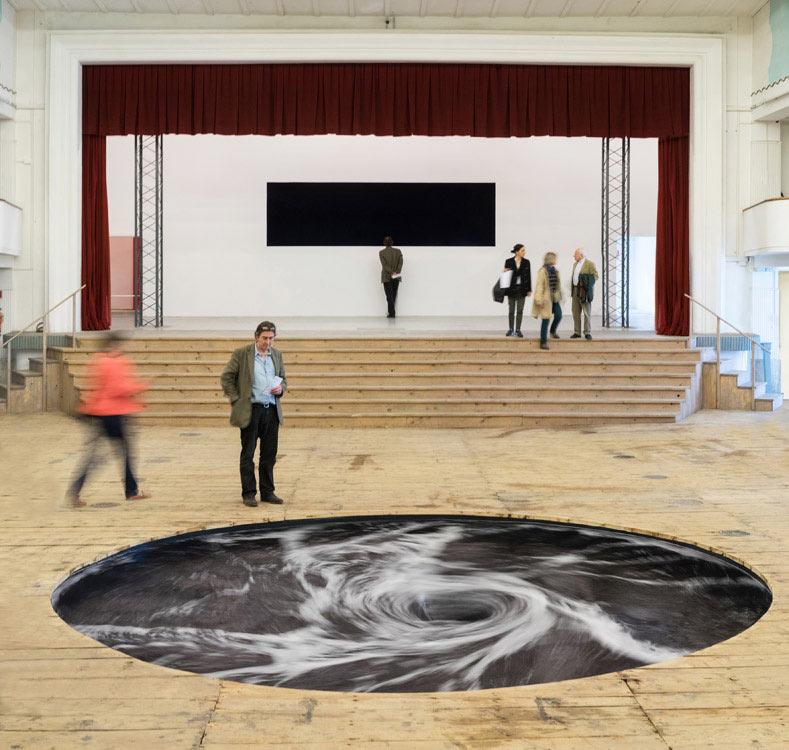 Perpetuo remolino de agua negra instalada en el piso de un antiguo cine en Italia