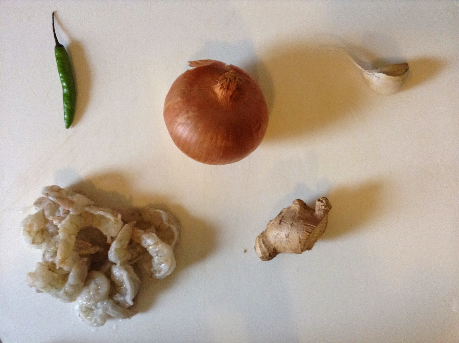 Shrimps, chili pepper, onions, garlic on a white chopping board