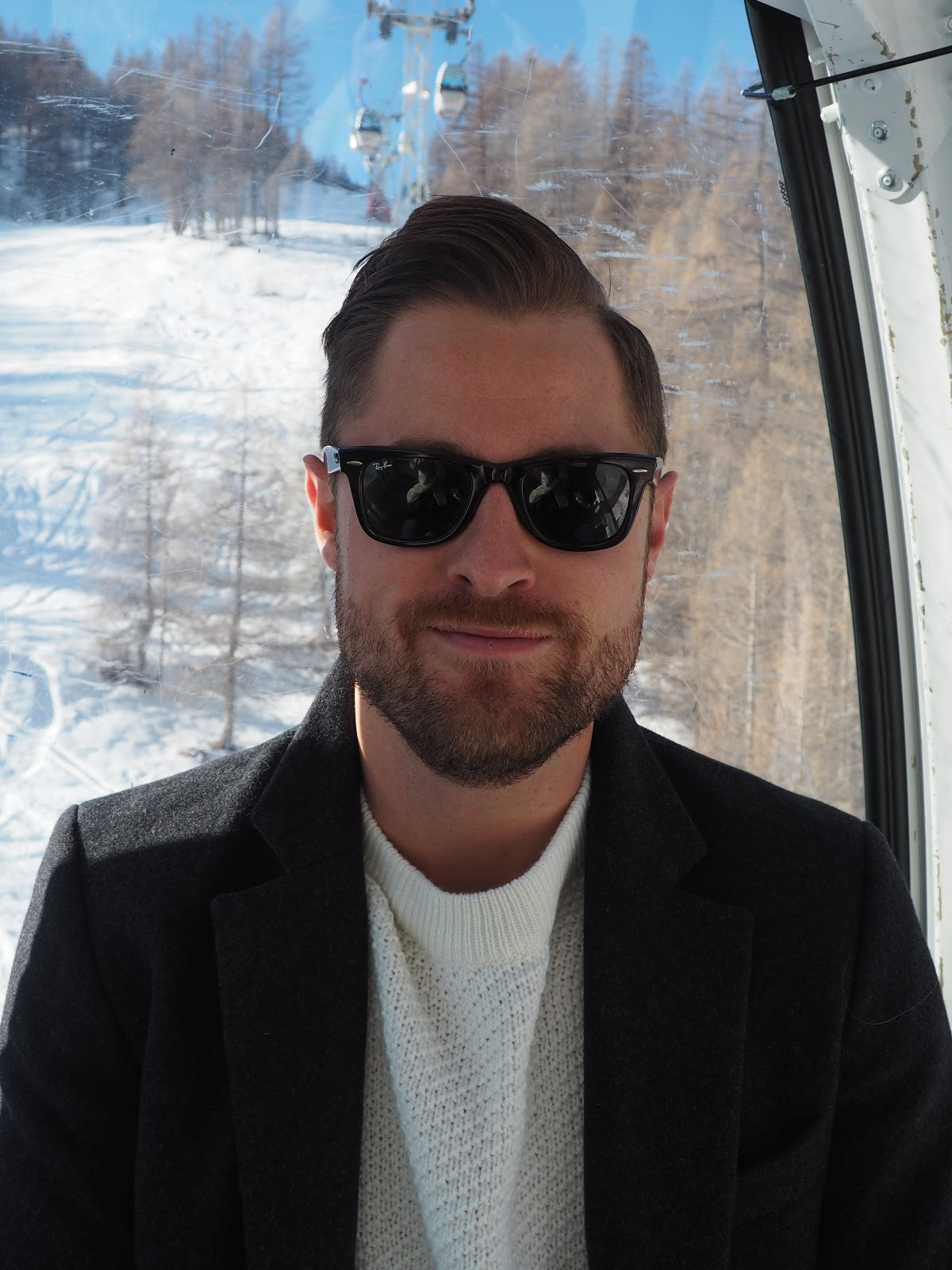 Man wearing ray ban sunglasses in a cable car against snowy mountains